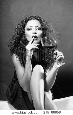 Closeup of one pretty sensual mysterious young brunette sexy woman with long curly hair and bright makeup in dress sitting in studio drinking red wine from glass on black background vertical picture