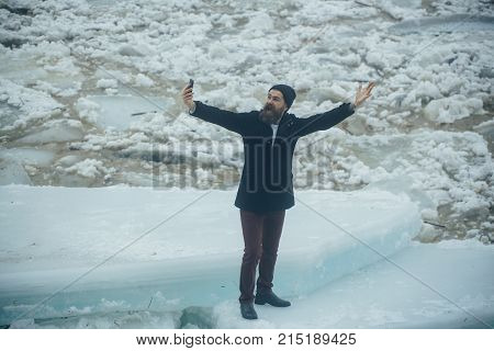 man with frozen hummock and mobile phone. Cracked ice background and guy in Christmas. Cold weather and ice age. Man with beard make selfie photo at ice block. Winter holiday and new technology.