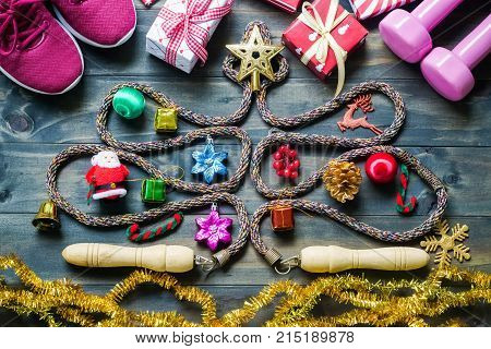 Fitness healthy and active lifestyles greeting card concept dumbbells sport shoes skipping rope or jump rope in the form of christmas tree with Christmas decoration on wood background retro tone. Exercise Fitness and Working Out Merry Christmas and Happy