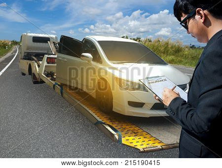 Insurance agent examining car after accident Tow truck delivers the damaged vehicle Sun light flare