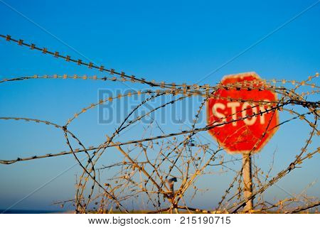 a large red road prohibiting stop sign stands on a deserted beach in front of him fence of metal wire fence wooden poles passage forbidden yellow sand blue sea shore clear blue sky summer warmth