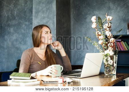 Designer Woman Working in Studio. Girl working with Creative Startup Project in Modern Loft. Generic Design Laptop on Wooden Table