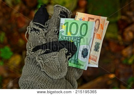 homeless man holds paper money in a tattered woolen glove