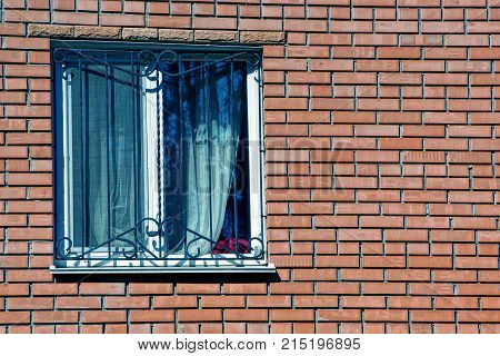 window with a curtain behind a lattice on a brown brick wall