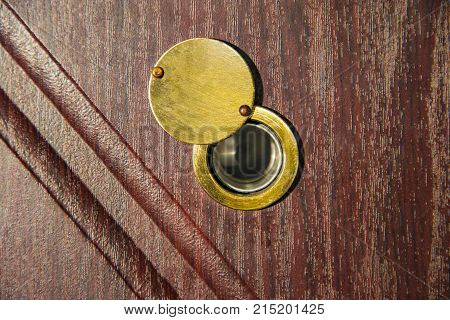 Peephole on wooden door - judas hole spyhole.