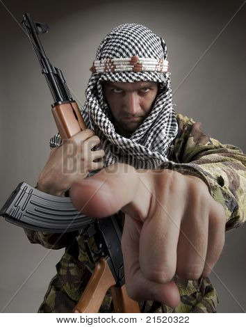 Serious eastern man with AK-47 pointing to you poster