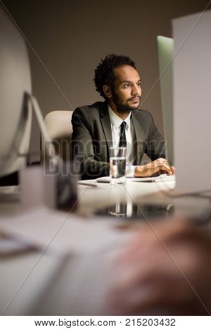 Portrait shot of mixed race bearded manager wearing stylish suit preparing presentation with help of computer while sitting at desk, interior of modern open plan office on background
