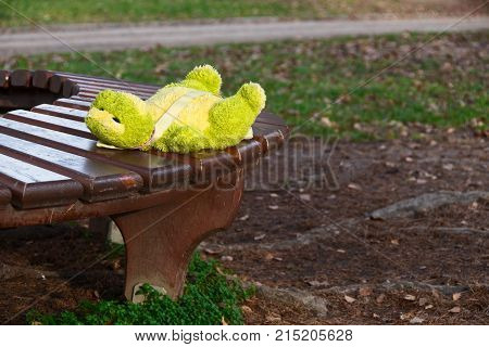 Lonely forgotten soft green frog toy, child backpack, lying on the bench in park waiting for owner, child to return