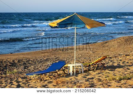 Yellow-blue beach umbrella and sun beds with table on a sandy beach by the sea.