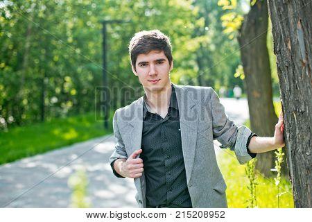 A Guy In A Jacket Near A Tree.