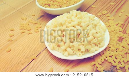 Macaroni boiled in plate and raw in bolw with raw around on wood desk for design macro photo graphy retro color tone.