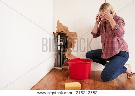 Middle aged woman with a burst water pipe phoning for help