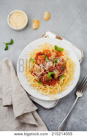Pasta spaghetti with tomato sauce parmesan cheese basil and meatballs on white ceramic plate on gray concrete or stone background. Selective focus. Top view.