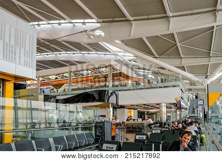 Heathrow Terminal 5 London UK - September 25 2017: Quiet seating area with people in terminal 5. Shot shows people sitting waiting for flights.