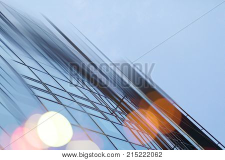 Abstract business modern city urban futuristic architecture background. Real estate concept, motion blur, reflection in glass of high rise skyscraper facade, toned blue picture with bokeh.
