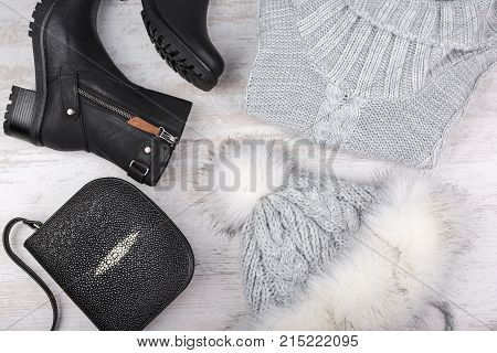 A set of fashionable winter women's clothing. Wool sweater, shoes, handbag and fur hat on white wooden background.