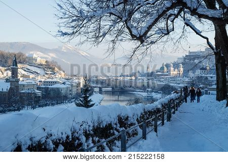 Salzburg Austria - January 1 2015: Walkers on a snowpath on Moenchsberg with view on Salzburg old city during winter