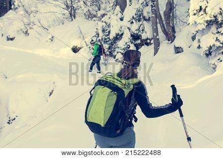 Female hiker looking across her should in winter forest. Freshly fallen snow.