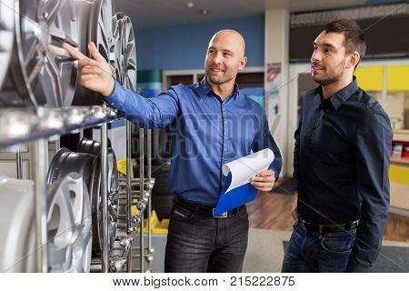 business, maintenance and people concept - male customer and salesman with clipboard showing alloy wheel rims at car repair service or auto store