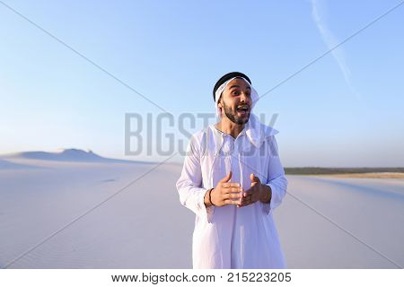 Charming young male Arab looks toward sun and goes up sand, examining landscapes of wide desert. Muslim smiles, leans over and takes sand in hands, blowing in wind. Swarthy, handsome Muslim with short dark hair dressed in kandura, long, spacious dress