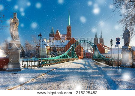 Tumski Bridge and Island with Cathedral of St. John and church of the Holy Cross and St. Bartholomew in the snowy overcast winter day in Wroclaw, Poland poster