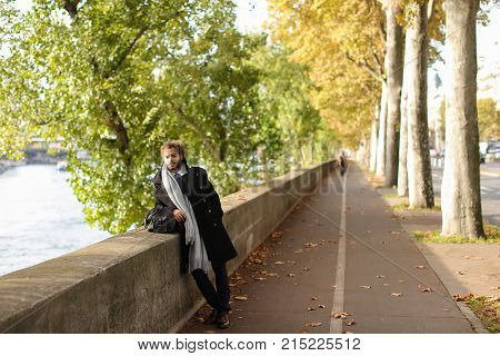 Young mulatto tourist going near Seine with bag in right hand. Handsome dreaming  guy has brown eyes, long black fleecy hair and beard. Concept of enjoying travelling alone and cheap tickets.