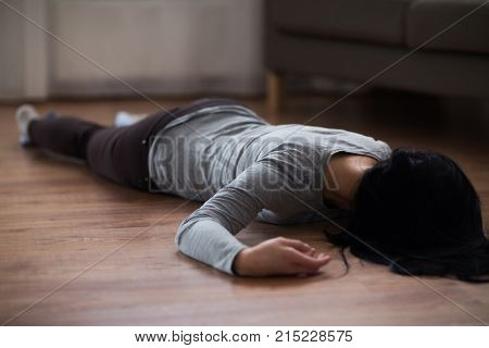 murder, kill and people concept - unconscious or dead woman body lying on floor at crime scene (staged photo)