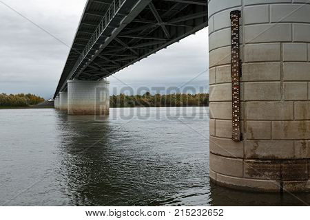 Bottom view of bridge supports over Kamchatka River - longest largest and most flooded river on Kamchatka Peninsula. View of bridge on overcast weather. Eurasia Russian Far East Kamchatka Region