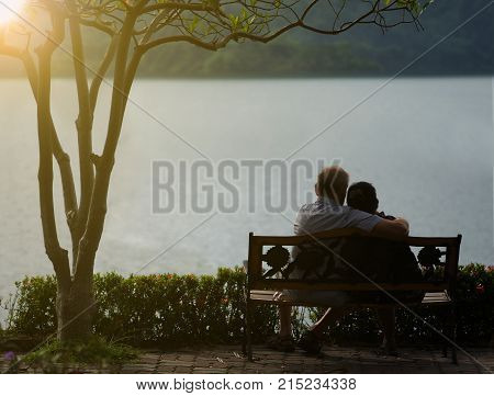 older couple with love and Take a hug at the waterfront in the garden.