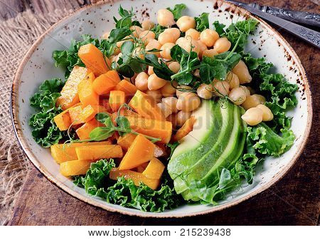 Healthy Vegetarian Nourishment Bowl With Chickpea, Green Pea, Pumpkin, Avocado, Lettuce And Pea Shoo