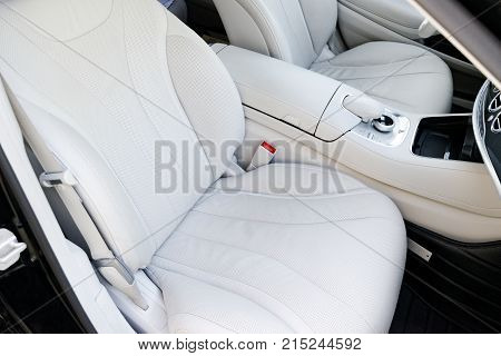 White perforated leather interior of the luxury modern car. Leather comfortable white seats and multimedia. Steering wheel and dashboard. automatic gear stick.