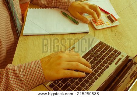 Businessman using a calculator to calculate the numbers. Businessman calculate finance and thinking about problem in home office - Retro color