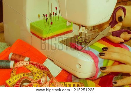 woman seamstress sitting and sews on sewing machine. Dressmaker work on the sewing machine. Hobby sewing as a small business concept. designer making a garment in her workplace poster