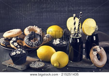 Charcoal lemonade with lemons on a dark wooden background