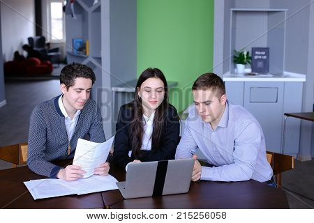 Three modern people, beautiful woman and two young men chatting and using laptop call classmate in skype through Internet, smiling and waving their hands in gadget's camera, sitting in modern day cafe. European-looking guy with fair hair and short hair dr