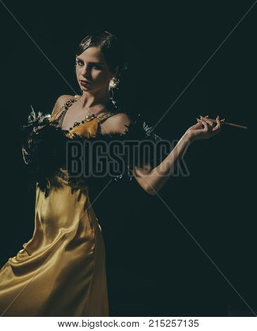 Girl in yellow dress boa fur with mouthpeice. Beauty and vintage fashion. Pin up pretty fashion model on black background. retro look and pinup. Woman with retro hair makeup and cigarette holder.