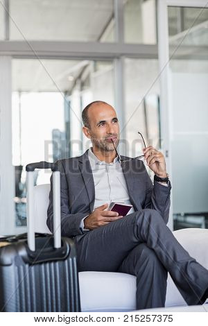 Pensive businessman sitting at airport waiting lounge with luggage. Successful mature business man in deep thought about new deal in business. Business on the move and travel concept.
