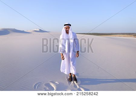 Handsome Arab man dances on spot and drives feet along soft white sand in middle of bottomless desert. Guy sheikh smiles and laughs, rejoices and jumps in national costume, which develops in wind. Swarthy Muslim with short dark hair dressed in kandura