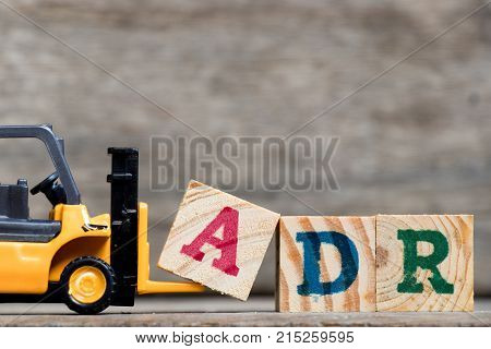 Yellow plastic forklift hold letter A to complete word ADR (Abbreviation of Adverse drug reaction) on wood background poster