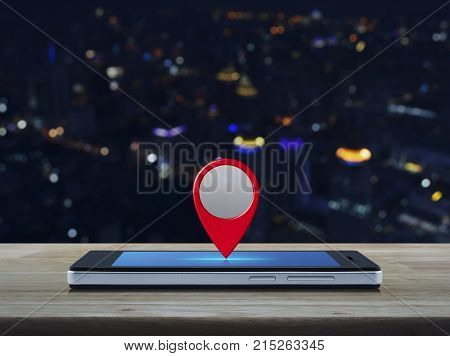 Map pin location button on modern smart phone screen on wooden table over blur colorful night light city tower Map pointer navigation concept