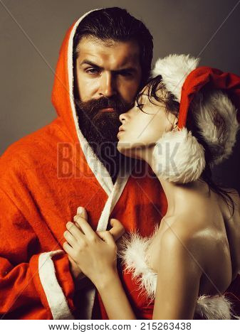 couple of bearded handsome santa claus man in new year coat and pretty sexy girl in christmas hat on grey background