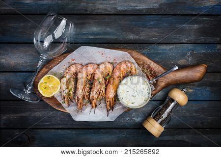 Large shrimp or langoustine with white sauce pepper-pot glass for the wine and half a lemon on a wooden board. Top view.