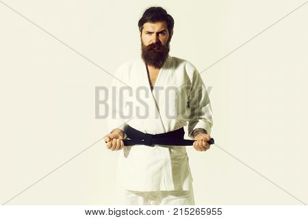 bearded karate man long beard brutal caucasian hipster with moustache in white kimono with black belt holds hands posing with serious face on grey background unshaven guy copy space
