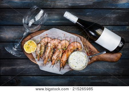 large delicious shrimp or langoustine with white sauce, bottle of wine, glass for the wine and half a lemon on a wooden board. Top view.