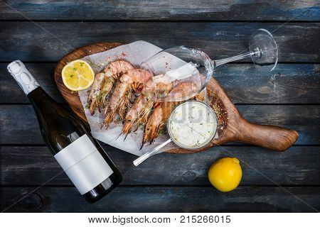 Large shrimp or langoustine with white sauce, bottle of wine, glass for the wine and half a lemon on a wooden board. Top view.