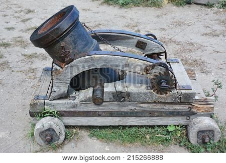 A mortar is a device that fires projectiles at low velocities and short ranges. Old rusty mortar or artillery gun on wheels. Cold Hybrid War concept.