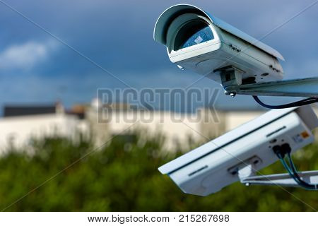 Security Cctv Camera Or Surveillance System With Residential Dwellings On Blurry Background