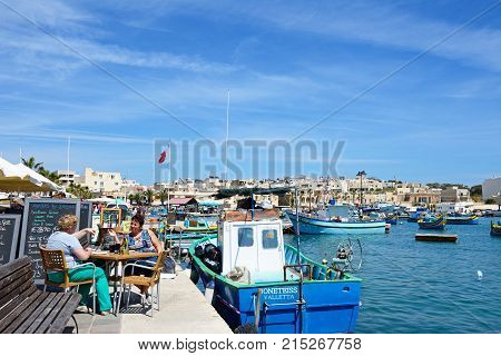 MARSAXLOKK, MALTA - APRIL 1, 2017 - Traditional Maltese Dghajsa fishing boats in the harbour with waterfront buildings to the rear and two women relaxing at a restaurant on the quayside Marsaxlokk Malta Europe, April 1, 2017.