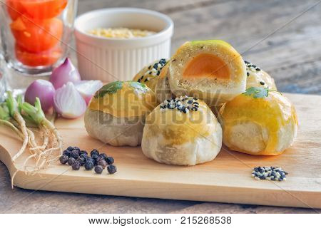 Delicious Chinese pastry or mooncake on wood cutting board with some ingredient on wooden table. Close up mooncake or Chinese pastry in side view with copy space. Homemade bakery concept of Chinese pastry for afternoon tea or coffee break.