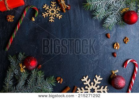Layout on a dark background with a place for an inscription, decorated with a Christmas tree branch, wooden snowflakes, Christmas toys, cinnamon sticks and nuts. View from above. Indoors.